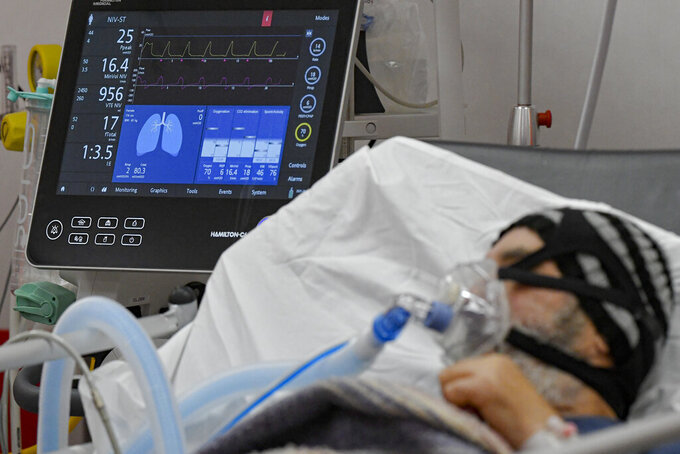 A man breathes through an oxygen mask in the emergency room, turned into a CODIV-19 unit due to the high number of cases, at the Bagdasar-Arseni hospital in Bucharest, Romania, Tuesday, Oct. 12, 2021. (AP Photo/Andreea Alexandru)