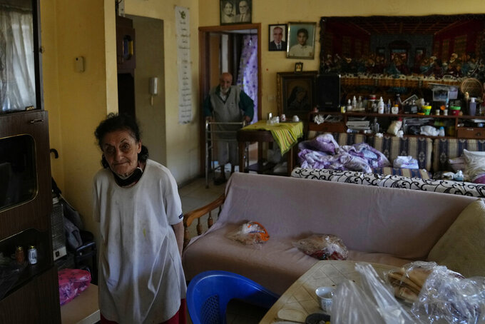 Marie Orfali, 76, left, and her husband Raymond, pose for a photograph in their apartment in Beirut, Lebanon, Tuesday, June 15, 2021. Tiny and bowed by age, Orfali makes the trip five times a week from her Beirut apartment to the local church, a charity and a nearby soup kitchen to fetch a cooked meal for her and her 84-year-old husband. (AP Photo/Hassan Ammar)