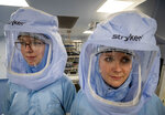 Two laboratory workers stand in a cleanroom of the BioNTech Corona vaccine production in Marburg, Germany, during a media day on Saturday, March 27, 2021. BioNTech, the Mainz-based company that invented the messenger RNA-based vaccine, is busily ramping up its production capabilities at the company's new production facility in Marburg. BioNTech originally expected the plant could turn out 700 million doses per year; it has since upgraded its expectations to a billion a year.  (AP Photo/Michael Probst)