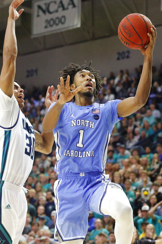Leaky Black (1) drives to the basket past North Carolina Wilmington's Jaylen Sims (30) during the second half of an NCAA college basketball game in Wilmington, N.C., Friday, Nov. 8, 2019. (AP Photo/Karl B DeBlaker)