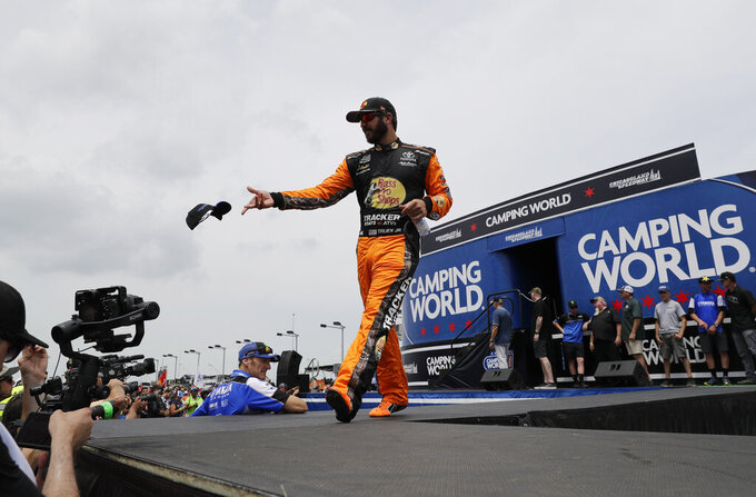 Martin Truex Jr.,throws a cap to the crowd during driver introductions before a NASCAR Cup Series auto race at Chicagoland Speedway in Joliet, Ill., Sunday, June 30, 2019. (AP Photo/Nam Y. Huh)