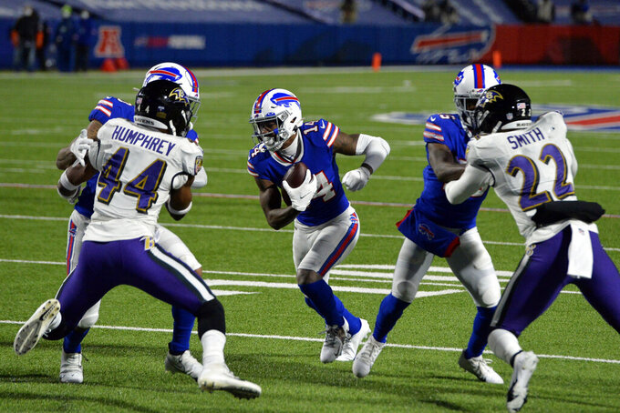 Buffalo Bills wide receiver Stefon Diggs (14) runs past Baltimore Ravens' Marlon Humphrey (44) and Jimmy Smith (22) for a touchdown during the second half of an NFL divisional round football game Saturday, Jan. 16, 2021, in Orchard Park, N.Y. (AP Photo/Adrian Kraus)