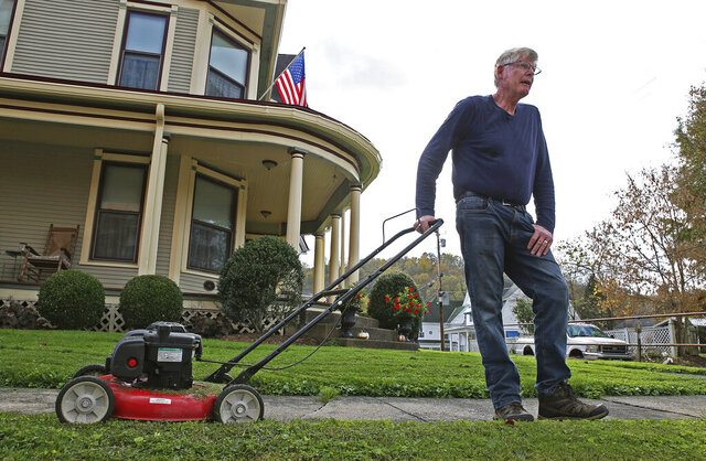 """James Musgrave discusses the increase in cases of the coronavirus in West Union, W.Va., Wednesday, Oct. 21, 2020. """"It's not our favorite thing,"""" said Musgrave referring to the pandemic as he took a break from mowing his front lawn. """"It's just one of those things you deal with and learn from and go on."""" (AP Photo/Kathleen Batten)"""