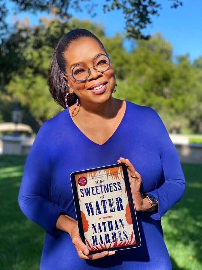 """Oprah Winfrey poses for a photo with an iPad, displaying the cover image for her Oprah's Book Club selection """"The Sweetness of Water"""" by Nathan Harris. The 29-year-old Harris, whose book comes out Tuesday, has said he wanted to show what it was like in the South after slaves were emancipated. A discussion between Winfrey and Harris will air July 23 on Apple TV+.  (Harpo, Inc. via AP)"""