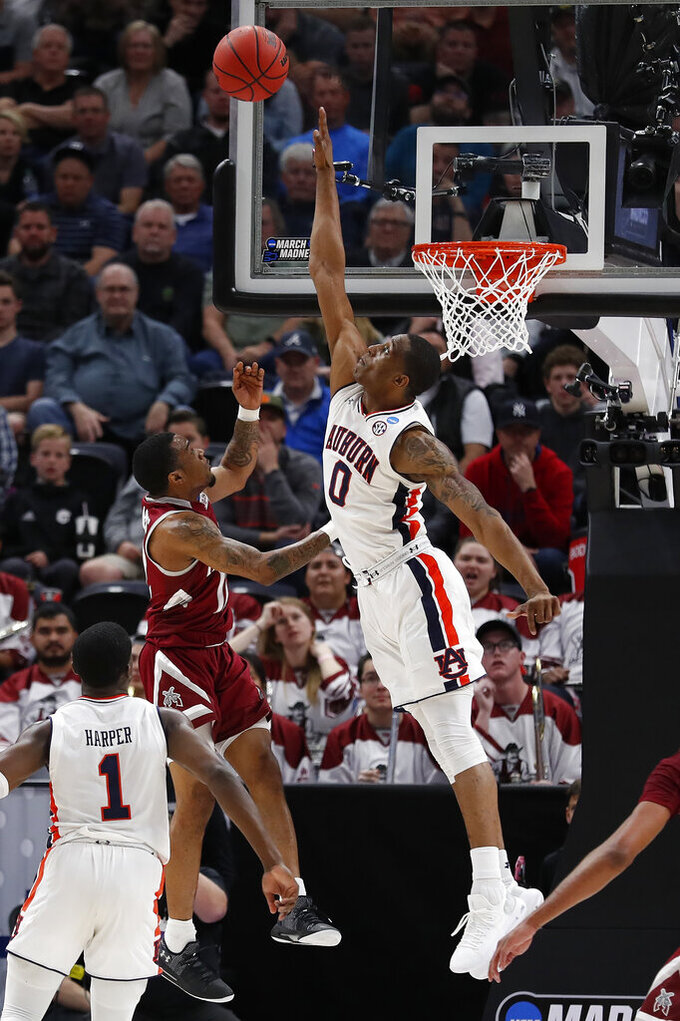 New Mexico State guard AJ Harris, left shoots over Auburn forward Horace Spencer (0) in the second half during a first round men's college basketball game in the NCAA Tournament, Thursday, March 21, 2019, in Salt Lake City. (AP Photo/Jeff Swinger)