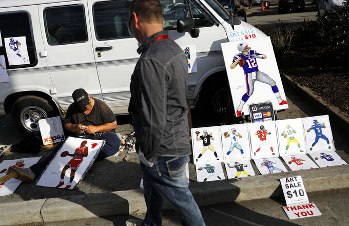 "Artist Michael ""Zebra"" Bailey, left, displays his paintings of famous sports figures near Mercedes-Benz Stadium ahead of Sunday's NFL Super Bowl 53 football game between the Los Angeles Rams and New England Patriots in Atlanta, Saturday, Feb. 2, 2019. Bailey travels the country going city to city selling his artwork out of his van. (AP Photo/David Goldman)"