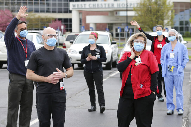 Healthcare workers wave and acknowledge members from the Crestview Presbyterian Church in West Chester Township, Ohio, as they participate in a prayer circle for front-line health workers Wednesday, April 22, 2020, in the parking lot at West Chester Hospital. (Kareem Elgazzar/The Cincinnati Enquirer via AP)
