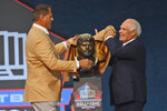 Jimbo Covert, a member of the Pro Football Hall of Fame Centennial Class, left, unveils the bust with his presenter Matt Suhey during the induction ceremony at the Pro Football Hall of Fame, Saturday, Aug. 7, 2021, in Canton, Ohio. (AP Photo/David Richard)