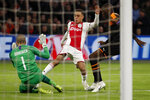 Valencia's goalkeeper Jaume Domenech saves on a shot by Ajax's Sergino Dest, center, during the group H Champions League soccer match between Ajax and Valencia at the Johan Cruyff ArenA in Amsterdam, Netherlands, Tuesday, Dec. 10, 2019. (AP Photo/Peter Dejong)