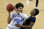 UCLA guard Johnny Juzang, left, fouls Marquette guard Koby McEwen (25) during the second half of an NCAA college basketball game Friday, Dec. 11, 2020, in Los Angeles. (AP Photo/Ashley Landis)