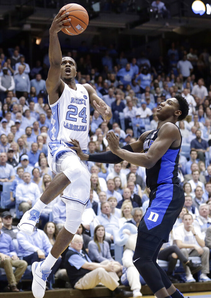 North Carolina's Kenny Williams (24) drives to the basket while Duke's RJ Barrett defends during the first half of an NCAA college basketball game in Chapel Hill, N.C., Saturday, March 9, 2019. (AP Photo/Gerry Broome)