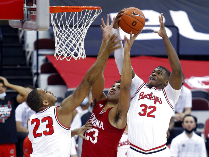 Indiana forward Trayce Jackson-Davis, center, reaches for a rebound between Ohio State forward Zed Key, left, and forward E.J. Liddell during the first half of an NCAA college basketball game in Columbus, Ohio, Saturday, Feb. 13, 2021. (AP Photo/Paul Vernon)