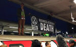 In this image taken from video, a protester stands of top of a train, in London, Thursday Oct. 17, 2019. Angry commuters scuffled with climate activists who climbed onto the roofs of trains, snarling services in the busy morning rush hours in the British capital. (ITN via AP)