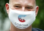 Rainer Knirsch, Telekom press spokesman, wears a mouth and nose protector with the app's logo at the beginning of a press conference on the 100-day Corona Warning App at the Federal Press Conference Center in Berlin, Germany, Wednesday, Sept. 23, 2020.(Kay Nietfeld/dpa via AP)