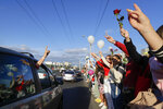 People greet each other waving flowers and white balloons as they gather to protest against the results of the country's presidential election in Minsk, Belarus, Thursday, Aug. 13, 2020. Crowds of protesters in Belarus swarmed the streets and thousands of workers rallied outside industrial plants to denounce a police crackdown on demonstrations over a disputed election that extended the 26-year rule of authoritarian President Alexander Lukashenko. (AP Photo/Sergei Grits)