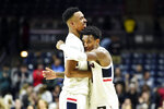 Connecticut's Tyler Polley (12) and Christian Vital (1) hug at the buzzer after beating Tulane in the second half of an NCAA college basketball game Wednesday, Jan. 8, 2020, in Storrs, Conn. (AP Photo/Stephen Dunn)