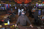 A dealer wears personal protective gear while working at the Golden Nugget Casino in Atlantic City, N.J., Thursday, July 2, 2020. Eager to hit the slot machines and table games after a 108-day absence, gamblers wore face masks and did without smoking and drinking Thursday as Atlantic City's casinos reopened amid the coronavirus pandemic that has drastically changed things both inside and outside the casino walls. (AP Photo/Seth Wenig)