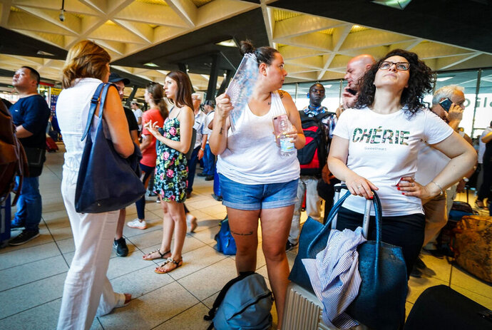 Passengers check train times at Naples' Central station, southern Italy, Monday, July 22, 2019. A suspected arson fire has forced cancellations of at least 42 high-speed trains in Italy on the heavily-traveled Milan-Naples corridor. (Cesare Abbate/ANSA via AP)