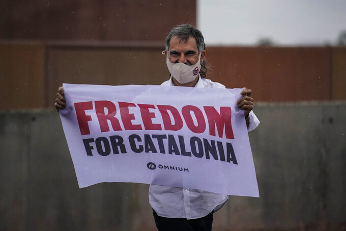 Jordi Cuixart, one of the Catalan leaders imprisoned for their role in the 2017 push for an independent Catalan republic, holds a banner at Lledoners prison in Sant Joan de Vilatorrada, near Barcelona, Spain, Wednesday, June 23, 2021. Nine separatists pardoned by the Spanish government are expected to leave the prisons where they were serving lengthy terms for organizing a bid for an independent northeastern Catalonia region nearly four years ago. Spain's official gazette published earlier in the day the government decree pardoning them. (AP Photo/Joan Mateu)