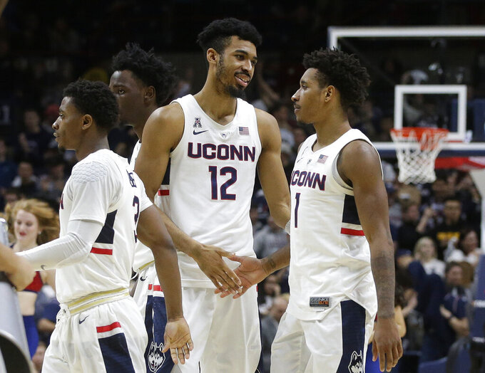 Connecticut's Tyler Polley (12) shakes hands with teammate Christian Vital (1) after defeating South Florida in an NCAA college basketball game, Sunday, March 3, 2019, in Storrs, Conn. (AP Photo/Steven Senne)