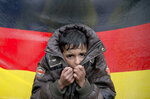 FILE - In this Wednesday, March 9, 2016 file photo a child tries to warm his hands, backdropped by Germany's flag as protesting migrants stage a sit in protest on the railway tracks at northern Greek border station of Idomeni. A new study estimates that at least 3.9 million unauthorized migrants, and possibly as many as 4.8 million, lived in Europe in 2017 with half of them in Germany and the United Kingdom. (AP Photo/Vadim Ghirda, file)