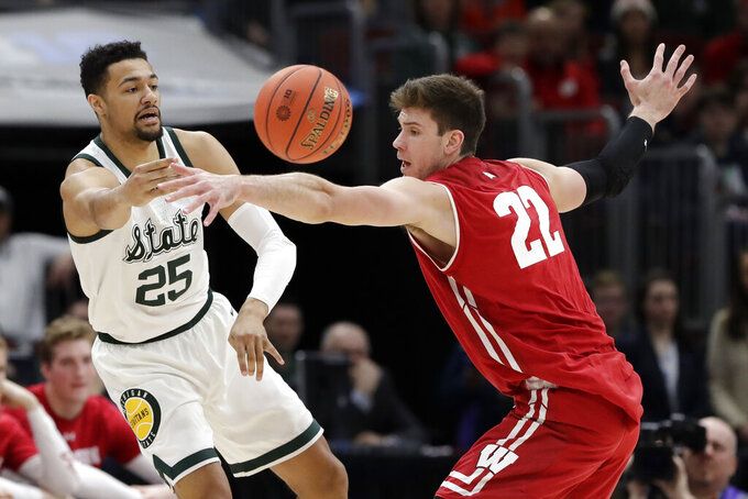 Michigan State's Kenny Goins (25) pass the ball around Wisconsin's Ethan Happ (22) during the first half of an NCAA college basketball game in the semifinals of the Big Ten Conference tournament, Saturday, March 16, 2019, in Chicago. (AP Photo/Nam Y. Huh)