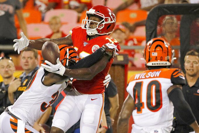 Kansas City Chiefs wide receiver Byron Pringle (13) tries to hold onto the ball against the defense of Cincinnati Bengals defensive back Tony Lippett (39) on a play that was called pass interference during the first half of an NFL preseason football game in Kansas City, Mo., Saturday, Aug. 10, 2019. (AP Photo/Colin E. Braley)