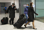 People wear masks following the outbreak of a new virus as people arrive from the International terminal at Toronto Pearson International Airport in Toronto on Saturday, Jan. 25, 2020. A Toronto hospital said Saturday it has a confirmed case of the deadly virus from China, Canada's first. Sunnybrook Health Sciences Centre said it is