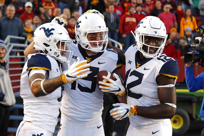West Virginia wide receiver David Sills V, center, celebrates with teammates after catching an 18-yard touchdown pass during the first half of an NCAA college football game against Iowa State, Saturday, Oct. 13, 2018, in Ames, Iowa. (AP Photo/Charlie Neibergall)