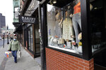 A pedestrian strolls past a fashionable boutique in the North End neighborhood of Boston, Tuesday, March 24, 2020. Mass. Gov. Charlie Baker ordered all nonessential businesses to close by Tuesday afternoon, and remain closed until at least April 7 in an effort to slow down the spread of the new coronavirus (AP Photo/Steven Senne)