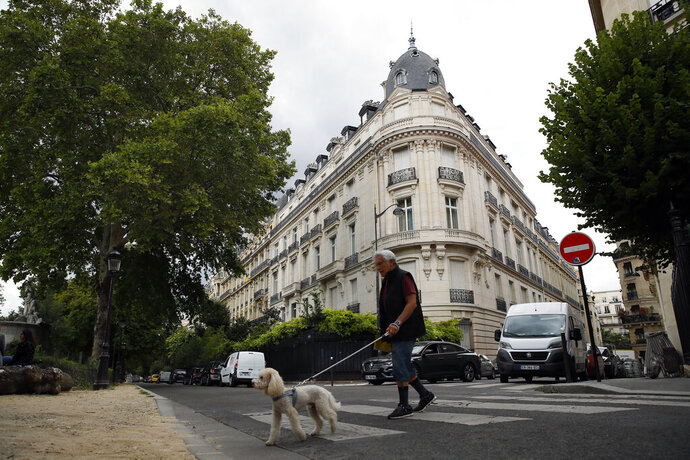 FILE - In this Aug.13, 2019 file photo, a man walks his dog next to an apartment building owned by Jeffrey Epstein in the 16th district in Paris, Tuesday, Aug. 13, 2019. Women who claim they were raped and sexually assaulted by an associate of Jeffrey Epstein are voicing disappointment at the apparent slow progress of a French police probe into their allegations and questioning the zeal of investigators who've made only limited efforts to track down other witnesses. (AP Photo/Francois Mori, File)