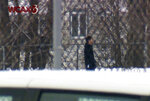 A man walks with a handgun on the grounds of Montpelier High School, Tuesday Jan. 18, 2018, in Montpelier, Vt. Police said the man, who tried to rob the Vermont State Employees Credit Union across the street from the school, was shot and killed by police on the school grounds. (WCAX-TV via AP)