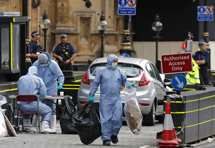 FILE - In this file photo dated Tuesday, Aug. 14, 2018, showing forensics officers at the scene after a car crashed into security barriers outside the Houses of Parliament in London, after colliding with a number of cyclists and pedestrians. The car driver whose car collided with several people before crashing outside Britain's Parliament has been convicted of attempted murder Wednesday July 17, 2019. (AP Photo/Frank Augstein, FILE)
