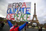 FILE - In this Dec.12, 2015, file photo, an activist holds a poster during a demonstration near the Eiffel Tower, in Paris, during the COP21, the United Nations Climate Change Conference. For America's allies and rivals alike, the chaos unfolding during Donald Trump's final days as president is the logical result of four years of global instability brought on by the man who promised to change the way the world viewed the United States. Alliances that had held for generations have frayed to a breaking point — from leaving the Paris climate accord and Iran nuclear deal to quitting the World Health Organization amid a pandemic. (AP Photo/Thibault Camus, File)