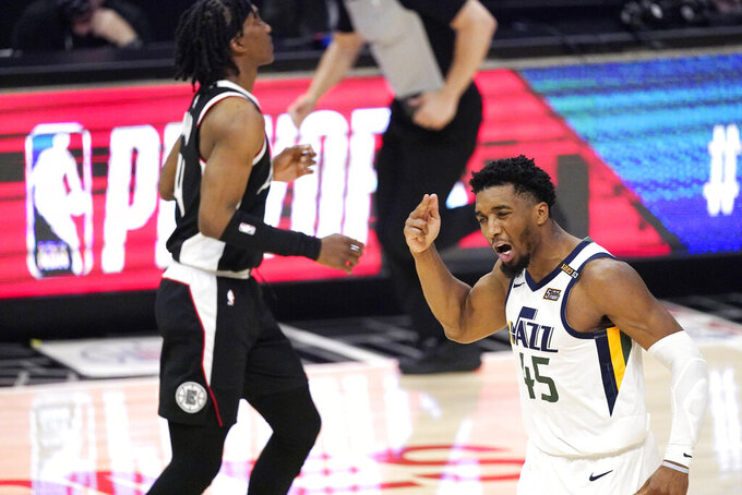 Utah Jazz guard Donovan Mitchell, right, reacts after a Los Angeles Clippers turnover as guard Terance Mann runs by during the second half in Game 6 of a second-round NBA basketball playoff series Friday, June 18, 2021, in Los Angeles. (AP Photo/Mark J. Terrill)