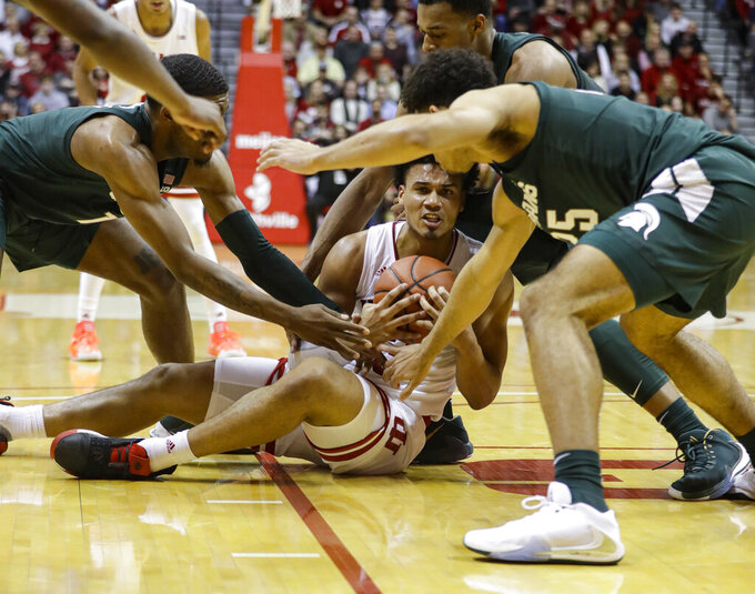 Indiana forward Justin Smith (3) is tied up by Michigan State forward Aaron Henry (11) and forward Malik Hall (25) in the first half of an NCAA college basketball game in Bloomington, Ind., Thursday, Jan. 23, 2020. (AP Photo/Darron Cummings)