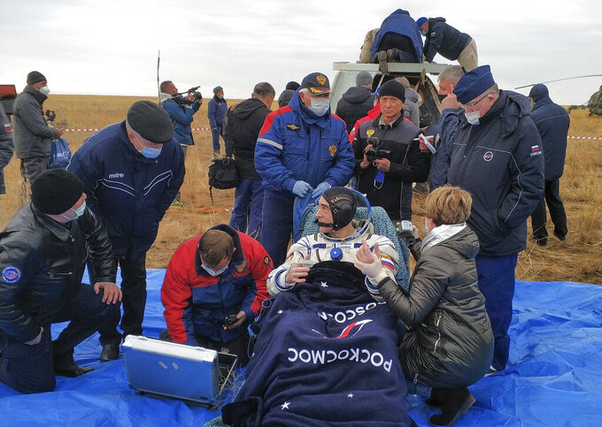 In this photo released by Rosaviatsiya, Roscosmos' cosmonaut Anatoly Ivanishin sits in a chair shortly after the landing near town of Dzhezkazgan, Kazakhstan, Thursday, Oct. 22, 2020. A trio of space travelers safely returned to Earth on Thursday after a six-month mission on the International Space Station. The Soyuz MS-16 capsule carrying NASA astronaut Chris Cassidy, and Roscosmos' Ivanishin and Ivan Vagner landed on the steppes of Kazakhstan southeast of the town of Dzhezkazgan on Thursday. (Rosaviatsiya via AP)