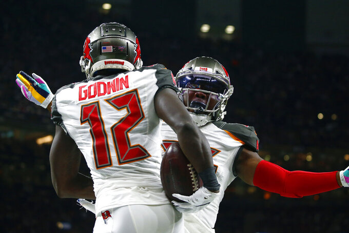 Tampa Bay Buccaneers wide receiver Chris Godwin (12) celebrates his touchdown with running back Peyton Barber in the first half of an NFL football game against the New Orleans Saints in New Orleans, Sunday, Oct. 6, 2019. (AP Photo/Butch Dill)