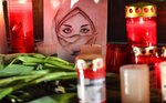FILE - In this Feb. 20, 2020, file photo, a picture of a woman is seen between candles and flowers at a monument on the market place during mourning for the victims of a shooting in Hanau, Germany. The rampage this week in Germany in which a gunman killed nine people with foreign backgrounds was the country's third deadly far-right attack in a matter of months. German leaders openly acknowledge there is a problem, but so far, identifying a solution has been elusive. (AP Photo/Martin Meissner, File)