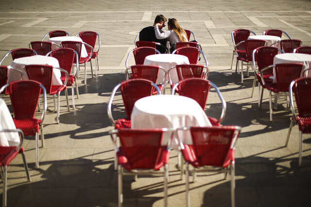Tourits sit in a barely empty restaurant terrace at the St. Mark's Square in Venice, Italy, Friday, Feb. 28, 2020. Authorities in Italy decided to re-open schools and museums in some of the areas less hard-hit by the coronavirus outbreak in the country which has the most cases outside of Asia, as Italians on Friday yearned for a return to normal life even amid fears that the outbreak could plunge the country's economy into recession. (AP Photo/Francisco Seco)