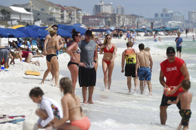 Beachgoers enjoy a sunny day in Destin, Fla., Wednesday, March 18, 2020. There's a new type of social policing out there that's developed almost as quickly as the viral disease that spurred its arrival. It's called