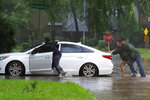 Residents push a stalled car as thunderstorms hit the Kingwood area flooding parts of Kingwood Drive, Tuesday, May 7, 2019, in Kingwood, Texas. Heavy rain is battering parts of southeast Texas prompting flash flood warnings, power outages and calls for water rescues.  (Jason Fochtman/Houston Chronicle via AP)