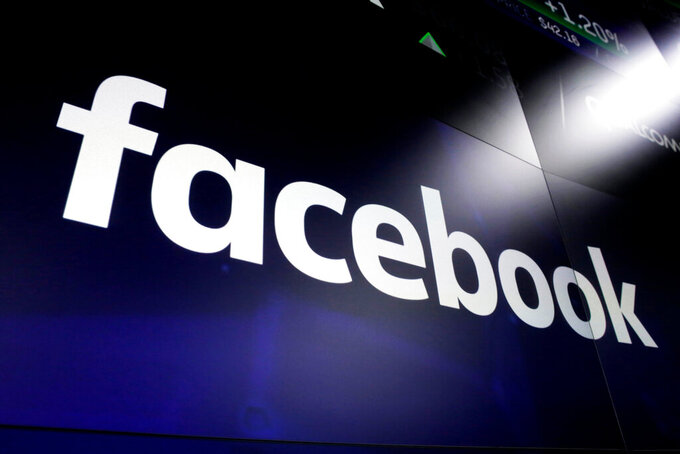 FILE - This March 29, 2018, file photo shows the Facebook logo on screens at the Nasdaq MarketSite, in New York's Times Square. Facebook said on Tuesday, Feb. 23, 2021, it lift its ban on Australians sharing news after a deal was struck on legislation that would make digital giants pay for journalism.(AP Photo/Richard Drew, File)