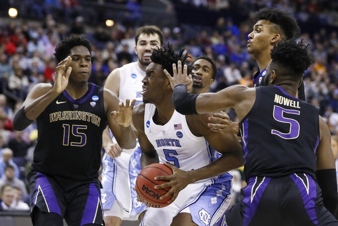North Carolina's Nassir Little, center, goes up for a shot against Washington's Noah Dickerson (15) and Jaylen Nowell (5) in the second half during a second round men's college basketball game in the NCAA Tournament, Sunday, March 24, 2019, in Columbus, Ohio. (AP Photo/John Minchillo)