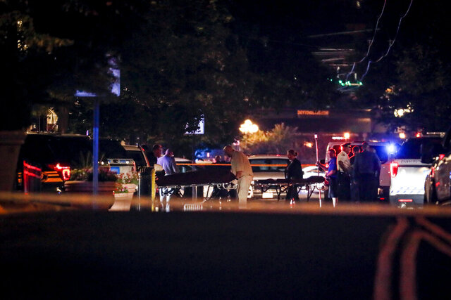 FILE - In this Aug. 4, 2019 file photo, bodies are removed from at the scene of a mass shooting in Dayton, Ohio. Several people in Ohio have been killed in the second mass shooting in the U.S. in less than 24 hours, and the suspected shooter is also deceased, police said. A mass shooting that left nine dead in Dayton is among Ohio's top stories for 2019 as selected by The Associated Press. Other big stories this past year in Ohio include the closing of a massive auto plant near Youngstown and the investigation of a Columbus doctor accused of ordering painkillers for dozens of patients who then died. Also making the list are the signing of a restrictive abortion bill, a lawsuit involving the nation's biggest drug distributors, an outbreak of tornadoes near Dayton and Ohio State's undefeated run to the college football playoffs.  (AP Photo/John Minchillo)
