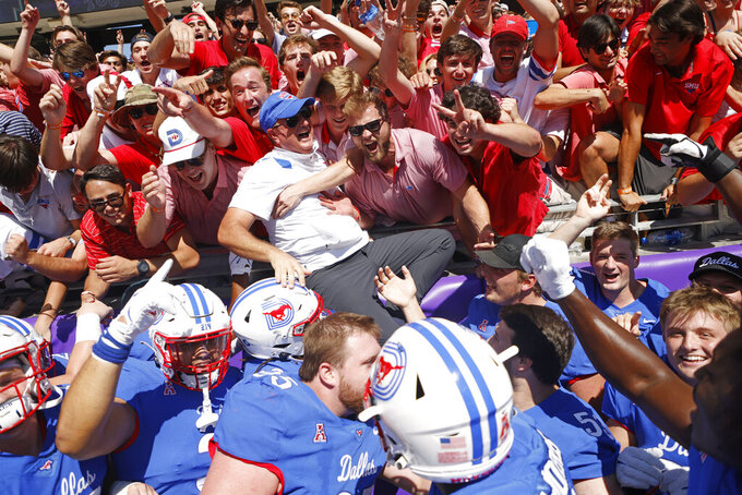 SMU head coach Sonny Dykes, center, in white, jumps into the stands after SMU defeated TCU during a NCAA football game in Fort Worth,Texas, Saturday, Sept. 25, 2021. (AP Photo/Michael Ainsworth)