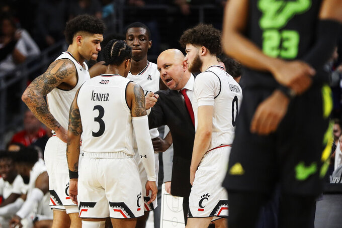 Cincinnati associate head coach Darren Savino, center, directs his players in the second half of the team's NCAA college basketball game against South Florida, Tuesday, Jan. 15, 2019, in Cincinnati. (AP Photo/John Minchillo)