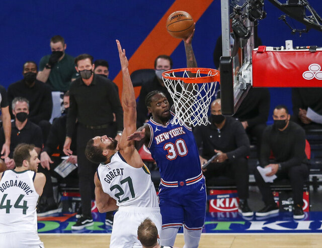 New York Knicks forward Julius Randle (30) dunks next to Utah Jazz center Rudy Gobert (27) during the first half of an NBA basketball game Wednesday, Jan. 6, 2021, in New York. (Wendell Cruz/Pool Photo via AP)