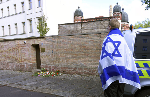 File---File picture taken Oct.10,2019 shows a person with a flag of Israel stands next to flowers and candles in front of a synagogue in Halle, Germany. A heavily armed assailant ranting about Jews tried to force his way into a synagogue in Germany on Yom Kippur, Judaism's holiest day, then shot two people to death nearby in an attack Wednesday that was livestreamed on a popular gaming site. (AP Photo/Jens Meyer,file)