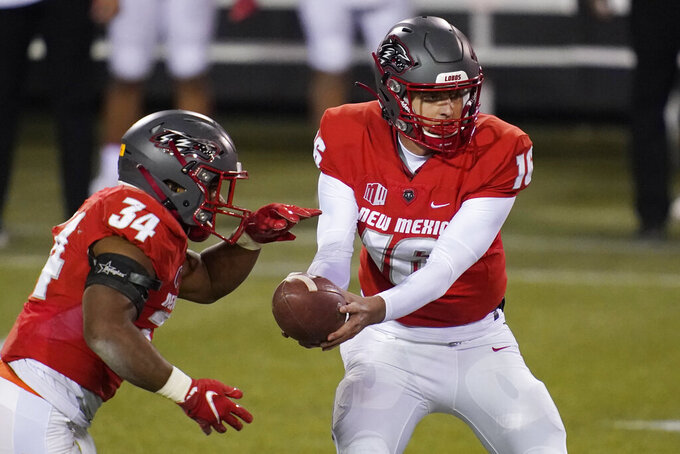 New Mexico quarterback Connor Genal (16) hands the ball off to running back Bobby Cole (34) during the first half of the team's NCAA college football game against the Wyoming, Saturday, Dec. 5, 2020, in Las Vegas. (AP Photo/John Locher)
